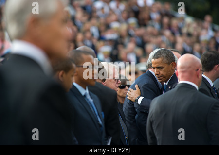 U.S. President Barack H. Obama hugs friends and family of those killed during a Navy Yard shooting at a memorial - Stock Photo
