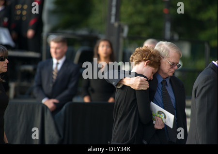 Friends and family of those killed at a Navy Yard shooting hug during a memorial for those killed during a shooting - Stock Photo