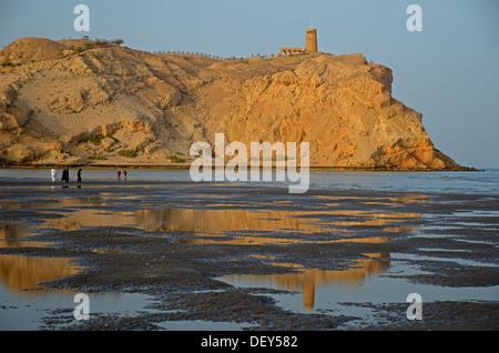 The rocky coast in Al Sawadi at the Gulf of Oman with a tower, Al Sawadi, Al Batinah, Oman - Stock Photo