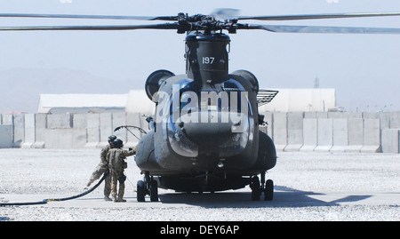 A U.S. Army CH-47 Chinook helicopter assigned to the 10th Combat Aviation Brigade stops for fuel at the forward - Stock Photo