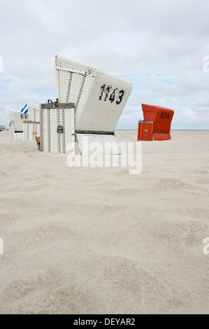 Roofed wicker beach chairs on the beach of St. Peter-Ording, North Frisia, Schleswig-Holstein - Stock Photo