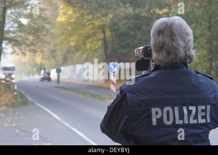 Policeman operating a radar gun, speed control, on 24/10/2012, Oberbergischer Kreis district, Lindlar, North Rhine - Stock Photo