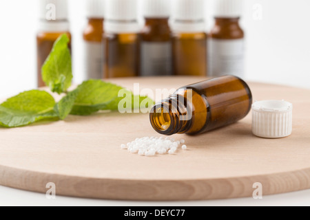 Open bottle with globules on a wooden board, homoeopathy, Lindlar, Bergisches Land, Germany - Stock Photo