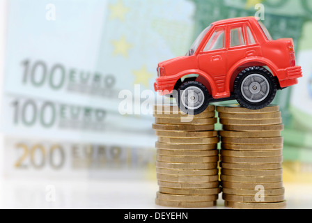 Miniature car on a stack of coins, symbolic image for car tolls - Stock Photo