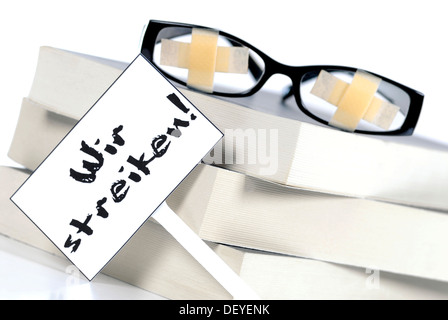Glasses with plasters on pile of books with a strike sign, symbolic image for students' strike, education problems - Stock Photo