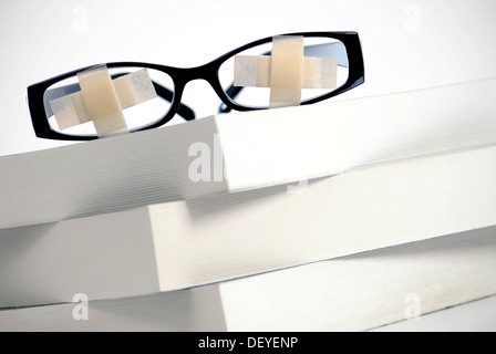 Glasses with plasters on pile of books, symbolic image for students' strike, education problems - Stock Photo