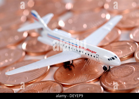 Miniature aircraft on cent coins, cheap airlines - Stock Photo