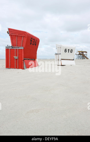 Roofed wicker beach chairs on the beach in front of a house on stilts, St Peter-Ording, Schleswig-Holstein, Germany - Stock Photo