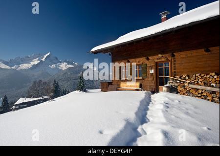 Wooden house on a snow-covered hill, Mt Alpspitze and Mt Zugspitze at back, Eckbauer, Garmisch-Partenkirchen, Upper - Stock Photo