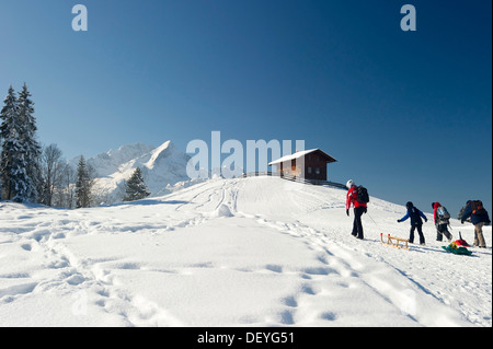 Sledgers and a wooden house on a snow-covered hill, Mt Alpspitze and Mt Zugspitze at back, Eckbauer, Garmisch-Partenkirchen - Stock Photo