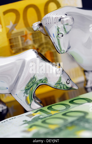 Stock market symbols bull and bear in front of euro banknotes, symbolic image for financial transaction tax - Stock Photo