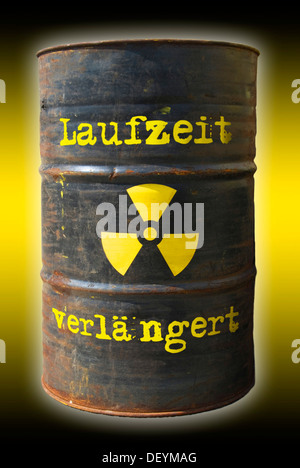 Rusty barrel with a radiation warning symbol and lettering 'Laufzeit verlaengert', German for 'extended runtime' - Stock Photo