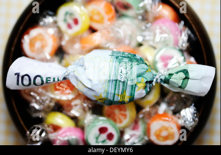Candy wrapped in a hundred-euro bill, symbolic image for premiums - Stock Photo