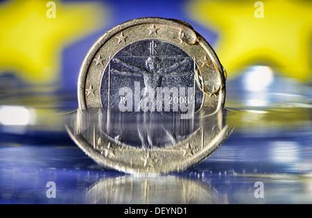 Italian eurocoin of water washed around, debt crisis in Italy, Italienische Euromünze von Wasser umspült, Schuldenkrise - Stock Photo