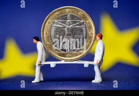 Italian eurocoin on the carrying of two paramedics, debt crisis in Italy, Italienische Euromünze auf der Trage zweier - Stock Photo