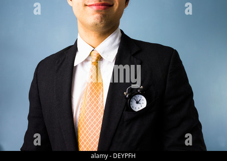 Young business man with a clock in his front pocket has time on his side - Stock Photo