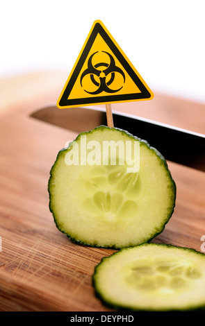Sliced cucumber with bio-hazard symbol, symbolic image for EHEC pathogens - Stock Photo