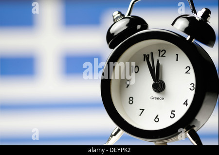 Five to twelve on an alarm clock display in front of Greek national flag, symbolic image, threat of impending national - Stock Photo