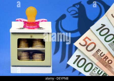 Miniature cooker with dummy and federal eagle, care money, Miniaturherd mit Schnuller und Bundesadler, Betreuungsgeld - Stock Photo