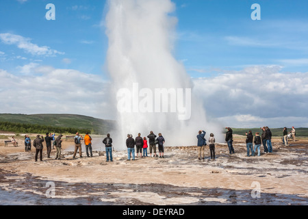 Tourists watching Great Geysir geyser erupting, Haukadalur valley, south western Iceland. - Stock Photo