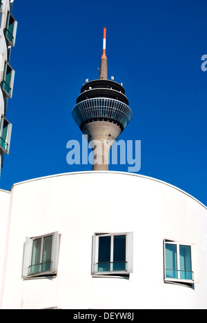 Rheinturm radio and television tower behind Gehry buildings in the Medienhafen Media Harbour, Duesseldorf - Stock Photo