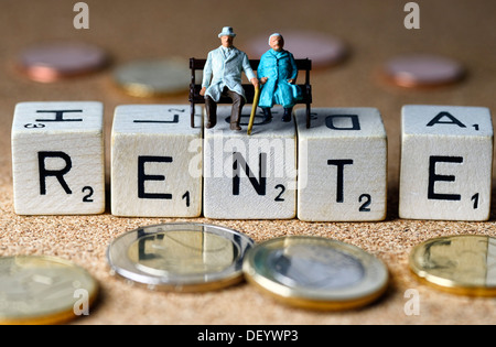 Miniature figures of a senior couple sitting on dice spelling out the word 'Rente', German for 'pension', symbolic - Stock Photo