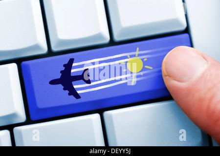 Finger on computer key with airplane symbol, on-line reservation of flights, Finger auf Computertaste mit Flugzeugsymbol, - Stock Photo