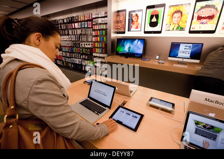 Teenage girl student shopping for an Apple Macbook laptop computer in the Apple Store, Grand Arcade Cambridge UK - Stock Photo