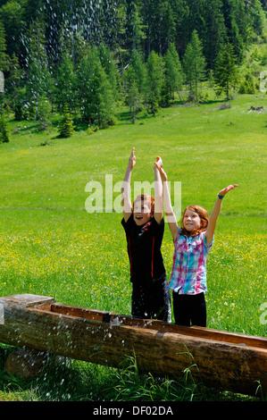 Children splashing water at an animal watering trough, Elendsalm, Klooaschertal valley near Bayerischzell, Blauberge - Stock Photo