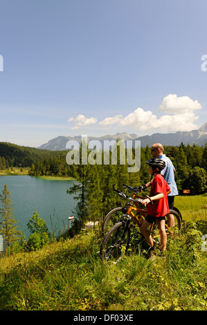 Cycling tour with mountain bikes, father and son in front of Lake Lautersee, Mittenwald, Karwendel Mountains, Werdenfelser - Stock Photo