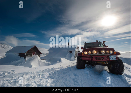 Super Jeep in front of the snow-covered Nýidalur Huts, Vatnajoekull Glacier, Icelandic Highlands, Iceland, Europe - Stock Photo