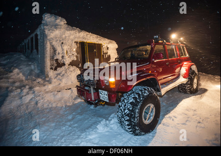 Super Jeeps in front of the snow-covered and frozen Grímsvoetn Hut, snow storm, Icelandic Highlands, Iceland, Europe - Stock Photo