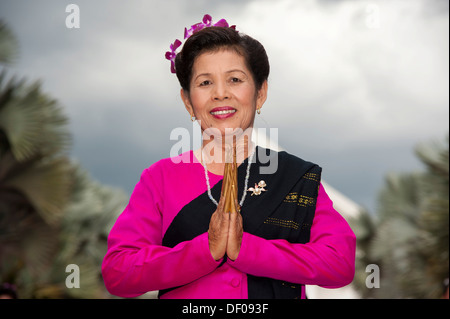 Traditional dance, smiling woman wearing traditional clothing making a gesture of greeting or Wai, Loi Krathong - Stock Photo