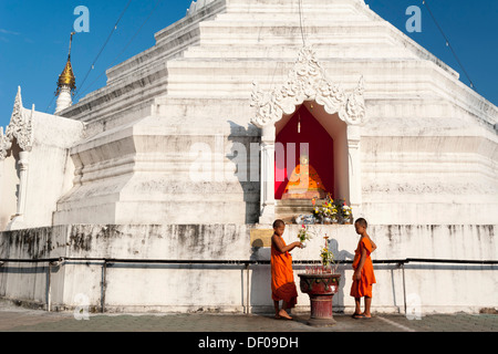 Young Buddhist monks with offerings in front of a Pagoda or Chedi, Temple complex of Wat Phra That Doi Kong Mu, - Stock Photo