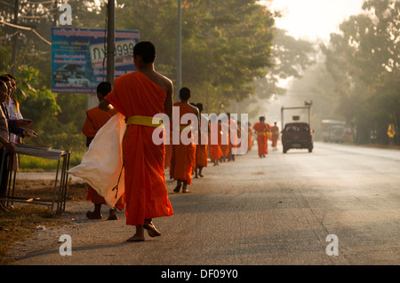 Morning alms round, young Buddhist monks from a monastery school, Sukhothai Province, Northern Thailand, Thailand, - Stock Photo