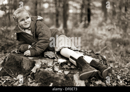 Five-year-old girl lying on a tree stump in the forest, in sepia - Stock Photo