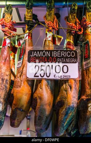 Pata Negra jamon iberico or spanish hams hang in La Boqueria market, Barcelona, Catalonia, Spain - Stock Photo