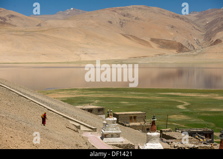 Monk walking down a scree slope towards chortons at the village of Korzok, with reflections in the high altitude - Stock Photo