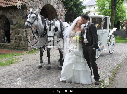 Berlin, Germany, a young married couple with a carriage in front of a church - Stock Photo