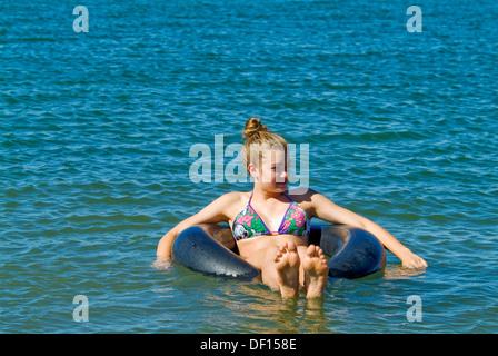 Teen Girl Floating On Inner Tube In River Stock Photo