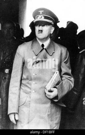 The image from the Nazi Propaganda! shows Adolf Hitler with a newspaper under his arm. Date and place unknown. Photo: - Stock Photo