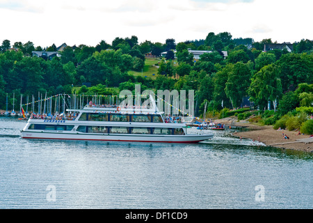 Tourist boat moves in to the shore to collect passengers on the Sorpe Reservoir, Germany - Stock Photo