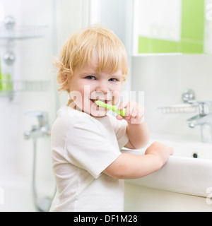 Kid boy brushing teeth in bathroom - Stock Photo