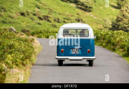 classic VW 1965 original British RHD 21 window caravette campervan travelling around the countryside, Devon, UK - Stock Photo