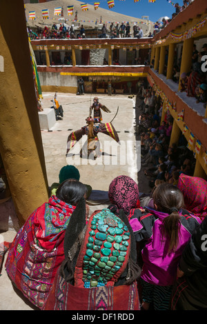 Changpa nomad woman with a turquoise headdress watching the Cham Dancing in the monastery courtyard, Korzok Gustor - Stock Photo
