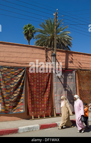 Moroccan women in traditional dress walking past hanging carpets for sale, near the Bahia Palace, Marrakech, Morocco - Stock Photo