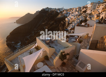 Looking down on to the town of Fira, lining the cliffs leading down to the sea at sunset, Santorini, Greece - Stock Photo