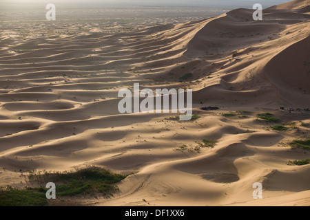 Looking down on to a small desert camp for tourists amidst rolling sand dunes of the Sahara Desert at sunrise, Erg - Stock Photo