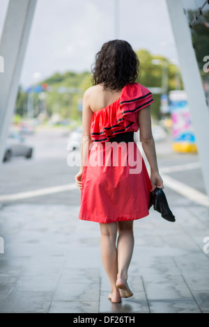Woman in red dress walking barefoot on square - Stock Photo