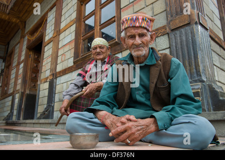 Elderly couple sitting in front of the Manu Temple, Old Manali, Manali, Himachal Pradesh, India - Stock Photo